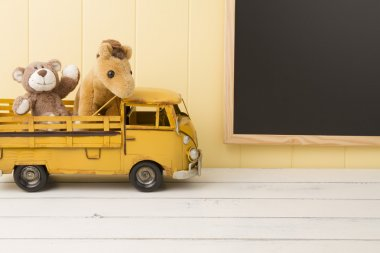 Two stuffed animal toys in a truck. A chalkboard in the background. Back to school