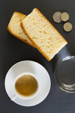 Breakfast: a coffee, two slices of pound cake and a glass of water. Some coins in the corner.