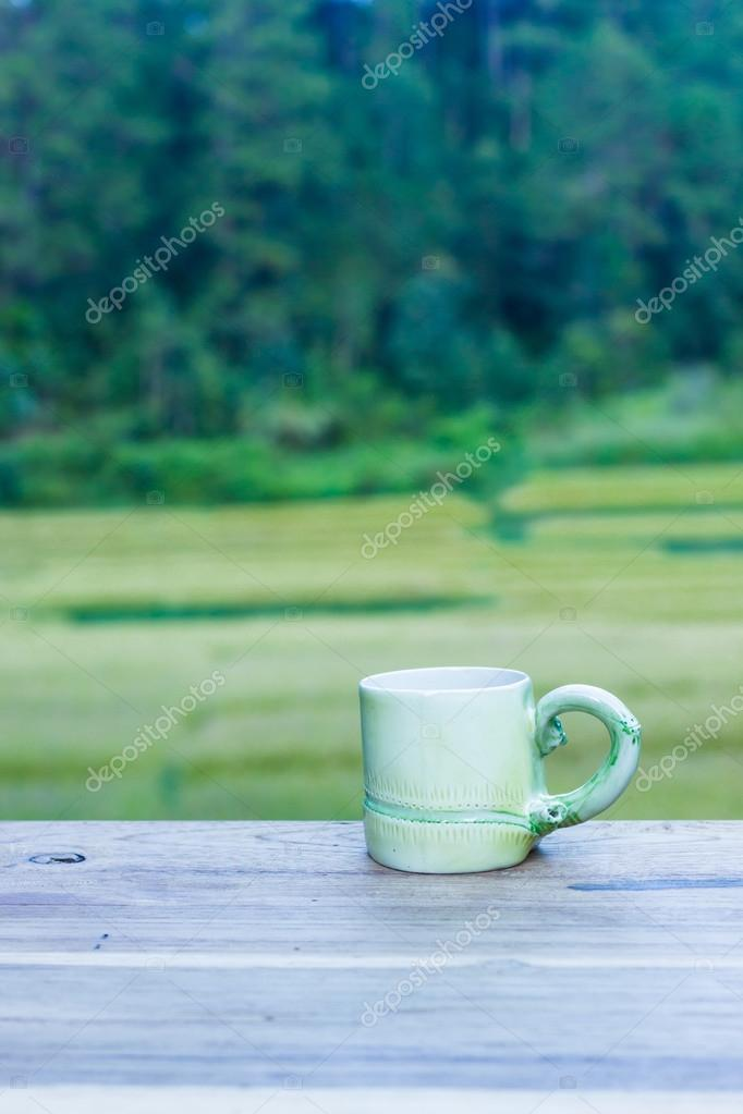 Cup with tea on table over rice fields.