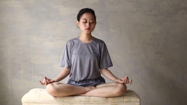 Asiatinnen praktizieren Yoga-Meditation in Innenräumen, Lotusposition. Kein Stress, Achtsamkeit, inneres Gleichgewicht