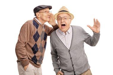 Senior man whispering something to friend