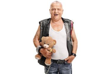 Mature punk rocker holding a teddy bear