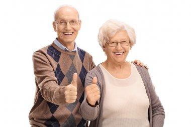Senior man and woman giving thumbs up