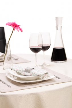 Vertical shot of a romantic dinner table with two glasses of red wine and a flower isolated on white background stock vector