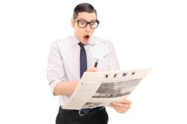 Man reading news through magnifier