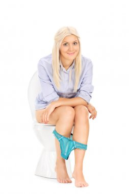 Girl peeing seated on toilet