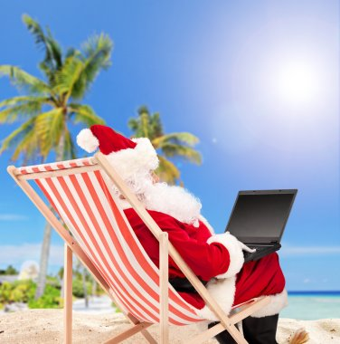 Santa with laptop on beach