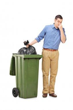 Man throwing out bag of trash