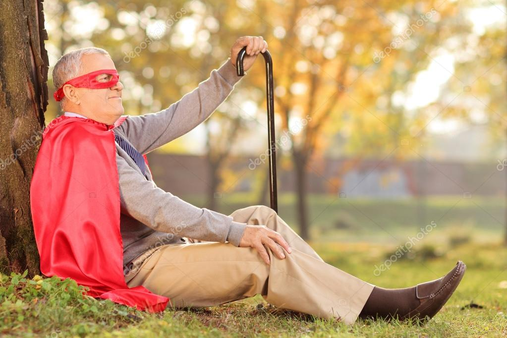 Old man sitting outdoor in superhero costume