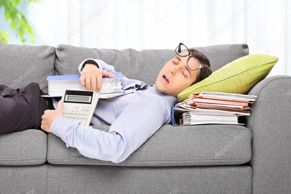 Tired employee sleeping on a sofa in an office on a pile of documents