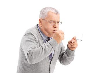 Senior smoking cigar and coughing