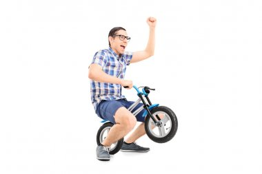 Young man riding small bike