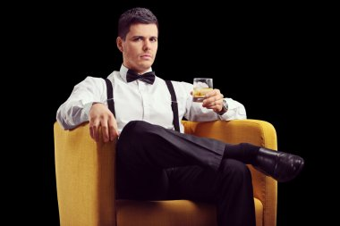 Man in armchair drinking whiskey
