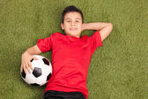 Photo Youngster lying and holding football