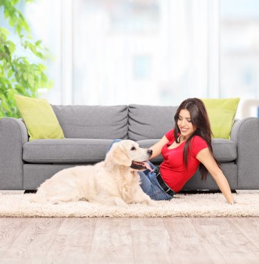 Young woman petting dog at home