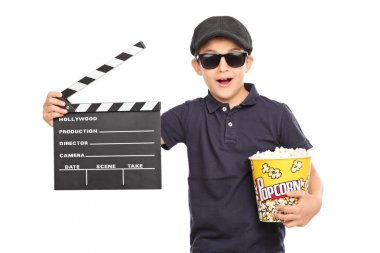 Little kid with a beret and sunglasses holding a box of popcorn and a movie clapperboard isolated on white background stock vector