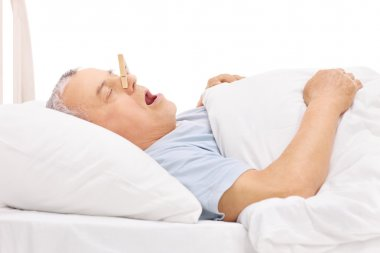 Senior sleeping with a clothespin on nose