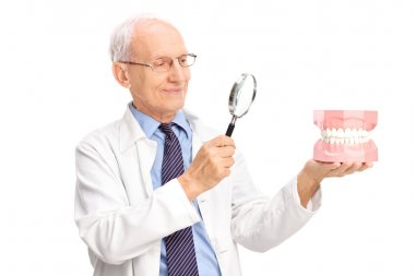 Dentist examining a denture with magnifying glass