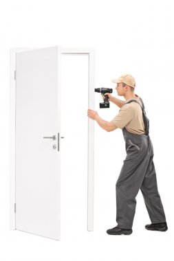 Young worker installing a door