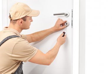Locksmith installing a lock on a door