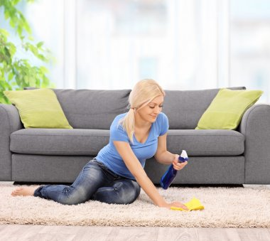 Woman cleaning a carpet with a rag at home