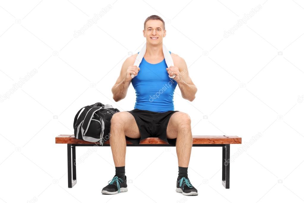 木製のベンチに座ったポーズの若...