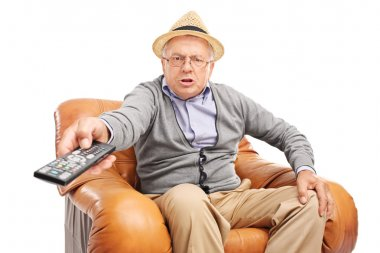 senior man pressing buttons on a remote control