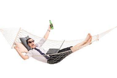 Businessman in hammock working on a laptop