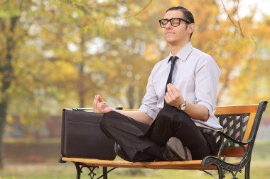 businessman meditating seated on a bench