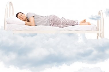 Young man sleeping on bed in clouds