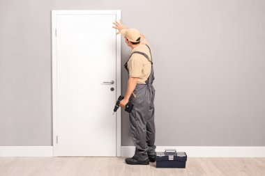 Young handyman installing a door