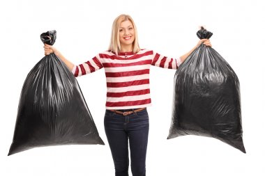 Cheerful woman holding trash bags