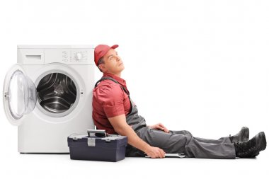 Exhausted plumber sitting by a washing machine