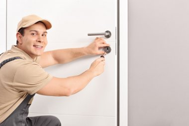 Cheerful locksmith installing a door lock