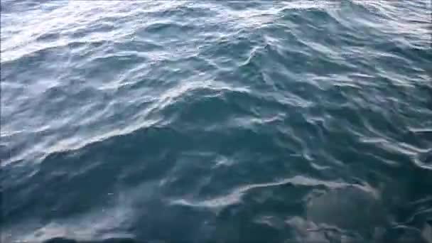 acqua di mare blu passando vista da una barca commovente con le scintille e riflessi di luce
