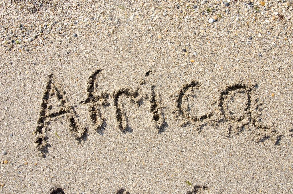 The word Africa handwritten in sand on a beach, ideal for internet or conceptual designs background with feet metaphor for communication, speech, message, mail, dialog, talk, contact, email, internet