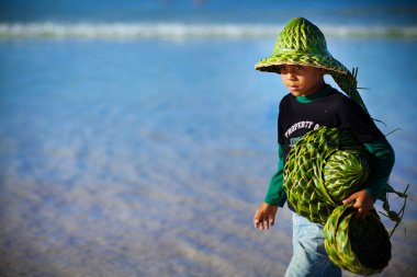 Young boy sells hats made of palm leaves, Dominican Republic