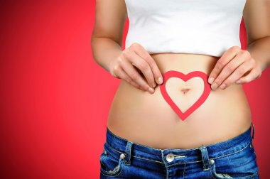Close-up portrait of a young woman holding a red heart shape on her stomach around her navel. Red background.