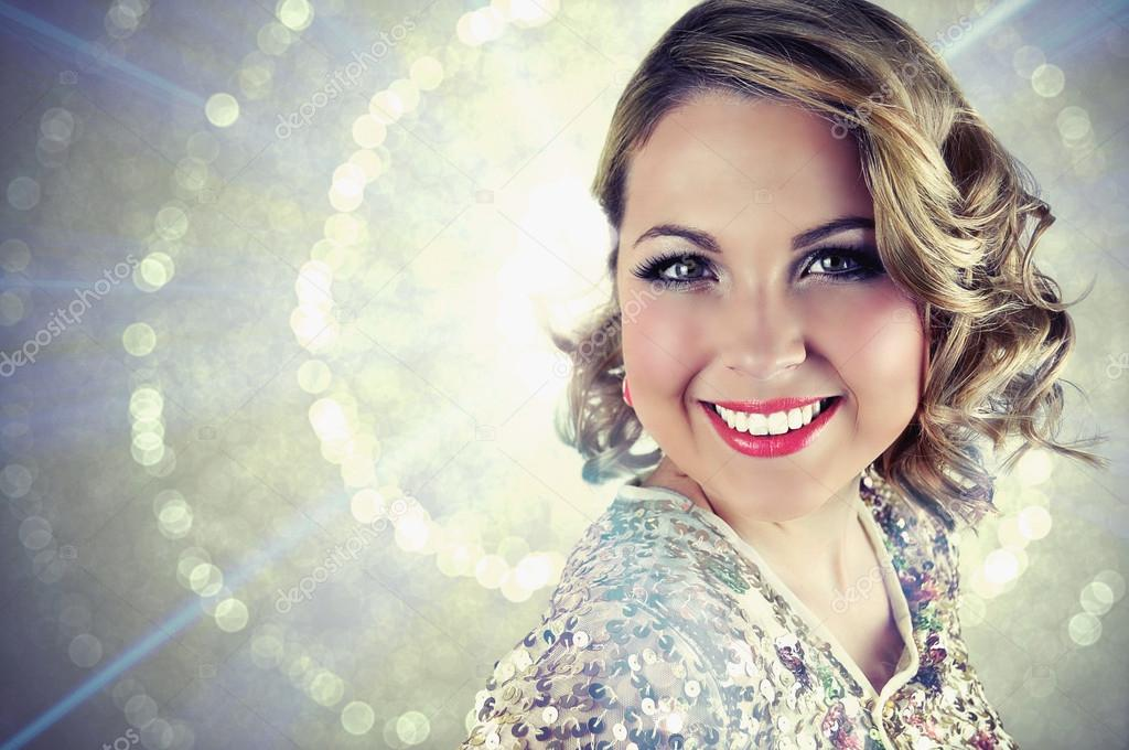 Beautiful smiling blonde woman with curly shoulder length hair wearing evening make-up and a golden sparkly sequin bolero.