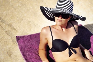 Beautiful woman wearing a black bikini, large black and white striped summer hat and black sunglasses is resting comfortably on a towel on the beach.