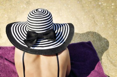 Elegant woman wearing a black bikini and a large black and white striped summer hat is lying comfortably on the towel on the beach.