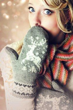 Beautiful blonde surprised woman wearing warm reindeer mittens.