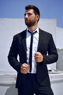 Attractive Spanish looking young man with a beard and dark hair and eyes is wearing a black suit and tie with a white shirt.