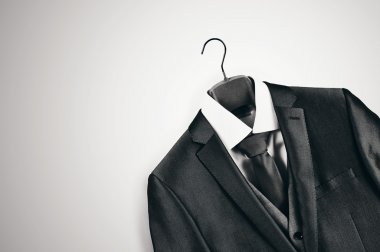 Black and white mens suit on clothes hanger.
