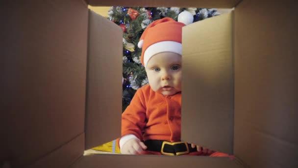 Kind öffnet Weihnachtsgeschenk in der Nähe eines geschmückten Weihnachtsbaums
