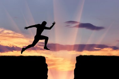 Runner athlete jumps over a precipice
