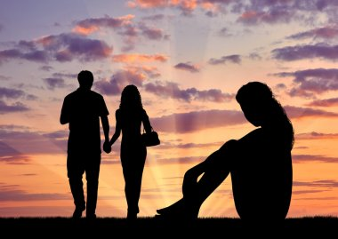 Silhouette  lonely woman looking at loving couple