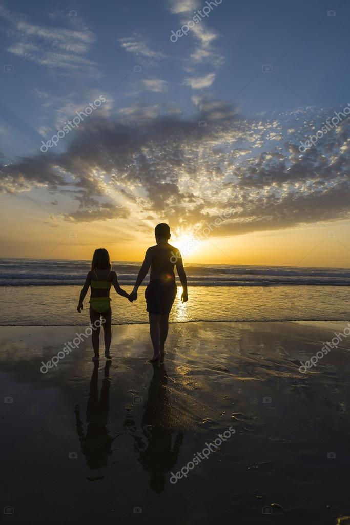Children bathing on the beach at dusk