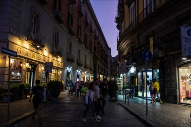 Naples, Italy - September 9, 2019: Via Chiaia, shopping street at night with people around in the old town of Naples, Italy