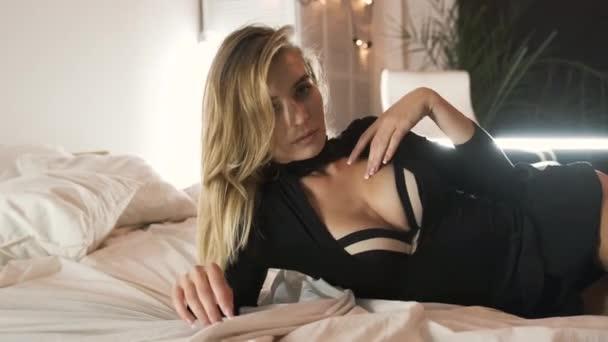 Sexy blondýny dívka v černé spodní prádlo eroticky pohybuje na posteli